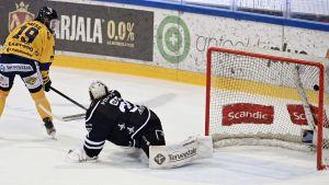 Robin Press lyfter in pucken bakom Karri Rämö i TPS-målet.