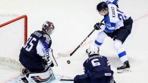 Kaapo Kakko med pucken framför USA:s mål, Jack Hughes försöker ta pucken av finländaren.