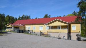 Ett avlångt gult trähus med rött tak.