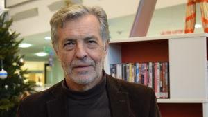 Jan-Erik Enestam, en man med grått hår, skägg och mustasch.