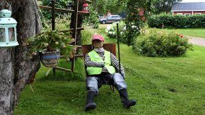 """En docka som ser ut som en människa med neonfärgad väst och röd keps sitter i en trädgård med """"ansiktet"""" mot kameran."""