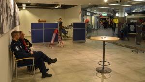 Två personer sitter i stolar i polisens popup-kontor i Hansakvarteret i Åbo centrum.
