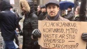 """En demonstrant i Estland visar ett plakat där det står; """"Journalister, domare, frivilligorganisationer, gynekologer, minoriteter - vem är nästa?"""""""