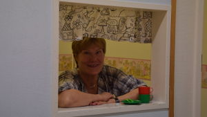 En kvinna ser ut genom ett hål i en innervägg. Hålet är ett minifönster med gardiner. Gjort för barn och deras lekar.
