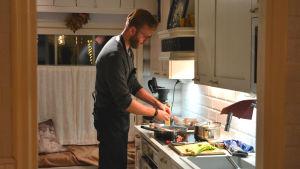 Jan- Christian Forsman står i köket och lagar mat, han skalar lök.