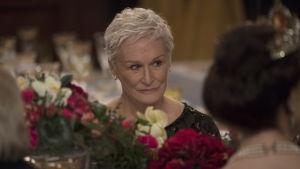 Närbild på Joan (Glenn Close) då hon sitter på Nobelmiddagen och ser irriterad ut.