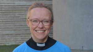 Kvinna med prästkrage och ljusblå tunika som ler
