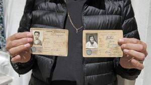 Israel Cohen med rötter i Israel visar upp sina föräldrars identitetskort från Djerba.