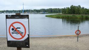 Skylt som visar att det är förbjudet att bada. I bakgrunden syns en avspärrad badstrand.