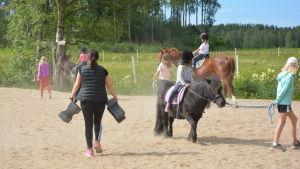 Hästar och ryttare på en sandplan.