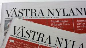 Två av Västra Nylands tidningar på varandra.