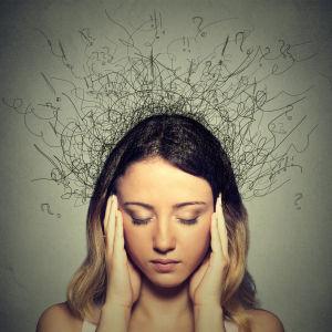 nainen uppoutuneena ajatuksiinsa kädet ohimoilla