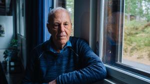 Caj Bremer står i mörkblå tröja vid ett fönster.
