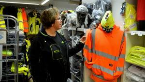 En kvinna i står i en butik omringad av gula och orangea arbetskläder.