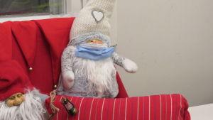 En jultomte i tyg. Tomten är på en soffa och har iklätts ett munskydd.