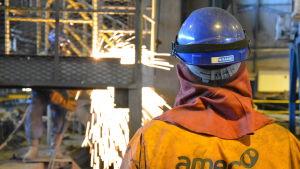En man med orange halare och vit skyddhjälm ser på när en annan person bränner sönder metallskrot i en fabrikshall.