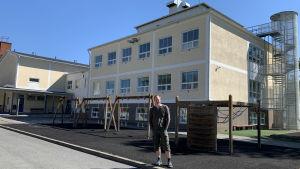 Toimittaja Jukka Kuosmanen koulurakennuksen edessä Lieksassa