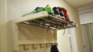 Tre par färggranna fotbollsskor på rad på en hatthylla.