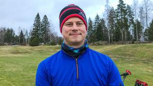 En man i blå jacka och rödsvart mössa står på en golfbana.