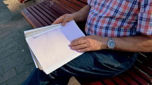 En man håller i ett anteckningsblock.