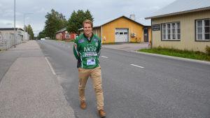 man i grön speltröja går på en gata