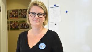 """en kvinna klädd i svart tröja och glasögon. Har en knapp/pin på bröstet där det står """"på svenska i Lojo"""""""