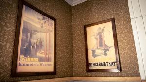 Kaksi vanhaa julistetta seinällä, jossa ruskea kuviollinen tapetti.