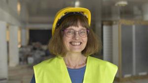 en leende kvinna ser in i kameran iklädd reflexväst och gul hjälm