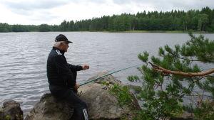 En äldre man metar vid en sjö.