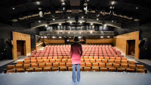 Kvinna i brun page ser ut över en tom teatersalong.