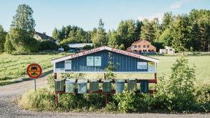 Maaseudulla tien laidassa postilaatikoita, niiden katoksessa teksti Kylä-Mukkulan kulttuurikeskus. Peltomaisemaa, taustalla navetta ja muita rakennuksia.