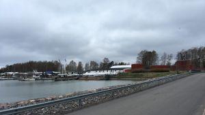 Bron till Björkholmen från Drumsö. Himlen är mulen, havet grått. På bilden syns båtar uppe på land och röda magasinbyggnader.