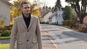 En man i ljusbeige jacka och svart polotröja står på en solig gata med småhus i olika färger.