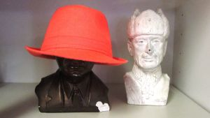 kaksi patsaspäätä ja toisella punainen hattu