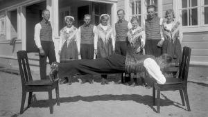 En man spänner sig mellan två stolar med bara sina fötter och armbågar. Bilden är tagen 1931 i Lill-Breds i Ingå.