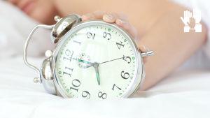 Person i sängen, väckarklocka i förgrunden.