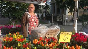 Anne Pekkinen står bland blommorna i sitt försäljningsstånd.