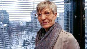 Kirsi Pimiä står framför ett fönster. Hon är Diskrimineringsombudsman i Finland.