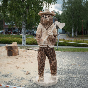 Puusta tehty veistos, karhu hattu päässä, kädessä kirves