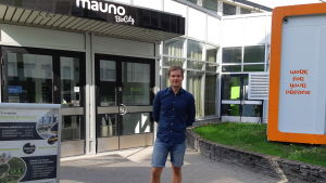 Ung man i blå skjorta och jeansshorts står med händerna bakom ryggen utanför byggnad
