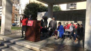 Kngressledamoten Terri Sewell syns i sin klarröda dräkt på svart utomhusmöte för demokraternas Doug Jones