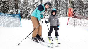 En kvinna och ett barn på slalomskidor i slalombacke. De ser in i kameran och ler.