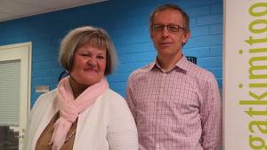 Mats Nurmio och Gilla Granberg poserar framför en blå bakgrund