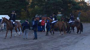 En grupp ryttare på hästar med skötare.