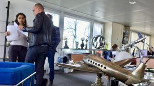 Bertrand Piccard talar med ett par anställda på hans stiftelse och i förgrunden ser vi en statyett av ett flygplan från mellankrigstiden.