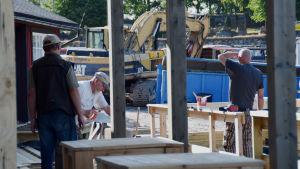 Byggarbetare jobbar vid ett bygge. En man sågar. I bakgrunden syns en grävmaskin.