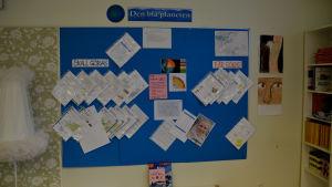På väggen hänger uppgifter i plastfickor som eleverna ska göra, plus en massa annan information om temat.