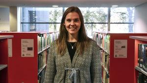 Amanda Audas-Kass står mellan bokhyllor i ett bibliotek och tittar in i kameran och ler.