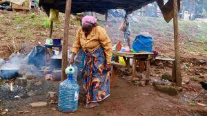 En försäljerska vid vägkanten i Nairobi häller vatten i en stor plastbehållare