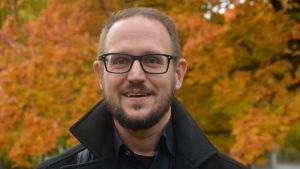 Man i glasögon och skägg ler mot kameran med höstlov i bakgrunden.